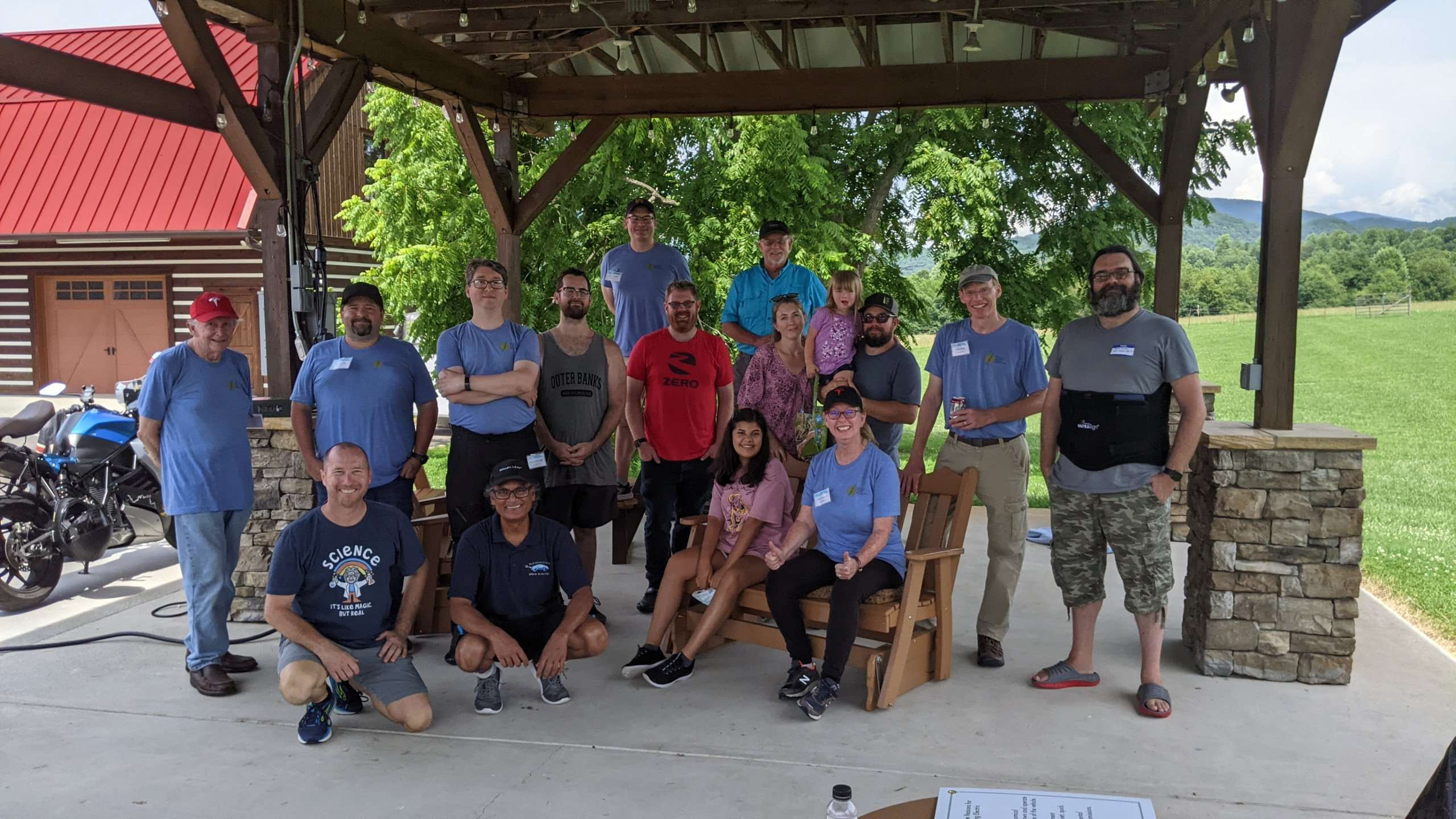 A group of about 13 electric vehicle enthusiasts stand under a wood pavilion smiling for a posed photo.