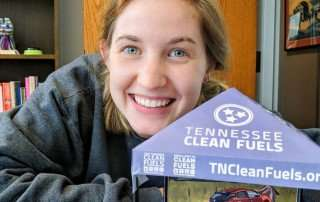 Sarah Roth, outgoing Special Project Coordinator at ETCleanFuels, poses with her mini-tent model